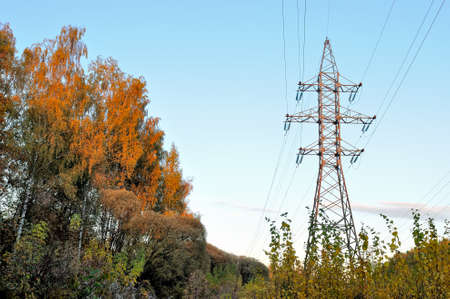 High voltage support, electricity transmission pylon surrounded by trees with yellow autumn foliage. Stok Fotoğraf