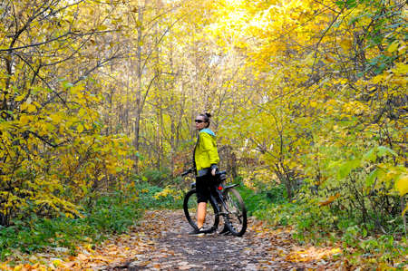 Caucasian fitness girl in a yellow jacket on a bicycle on a path in the autumn forest among yellow foliage and fallen leaves