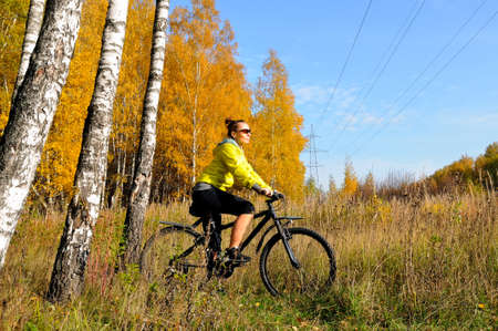 Young slim athletic girl on a bicycle in the autumn birch forest. Girl with a bicycle among birches with yellow leaves