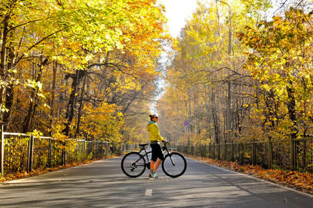 Slim caucasian girl in a yellow jacket poses with a bicycle on the road among the autumn forest