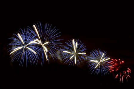 Flashes of blue, white and red festive fireworks against the night black sky
