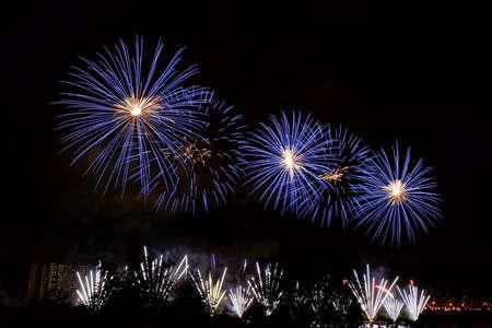 Destellos de fuegos artificiales azules y blancos contra el fondo de la ciudad nocturna y el cielo negro Foto de archivo