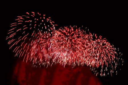Flashes of red fireworks and red smoke against the background of black sky