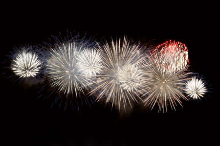 White, blue and red fireworks display on dark sky background. Brightly ñolorful fireworks on twilight background