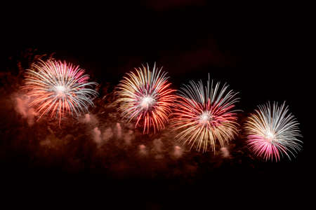 Des éclairs de feux d'artifice rouges, verts et blancs contre le ciel noir de la nuit. Feux d'artifice aux couleurs vives Banque d'images