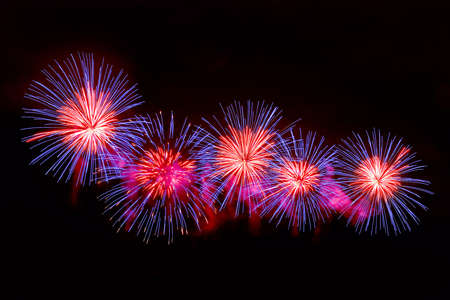 Amazing blue and red fireworks on dark background. Beautiful gold color fireworks display Imagens