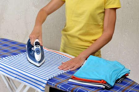 Woman ironing t-shirts on an ironing board using a modern electric steam iron Фото со стока