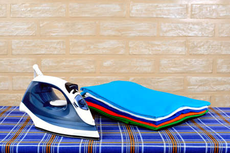 New modern electric steam iron and a stack of ironed t-shirts of various colors on ironing board on a brick wall