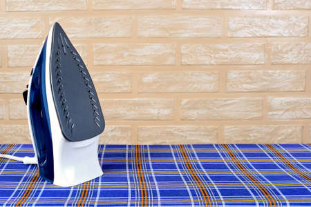 New modern electric steam iron on ironing board on a brick wall