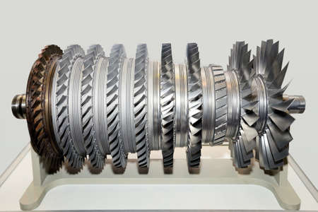Large metal industrial turbine with blades on a gray background.