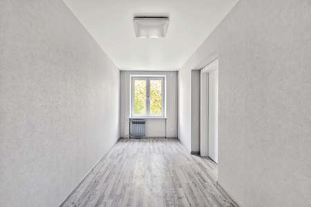 Empty room after repairs in an apartment building. Fresh renovated room with wooden floor Фото со стока