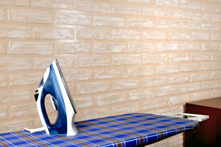 New modern electric steam iron on ironing board on a brick wall background