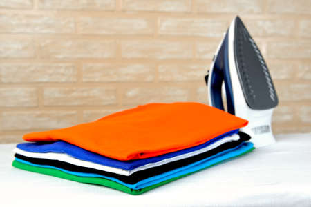 New modern electric steam iron and a stack of ironed t-shirts of various colors on ironing board on a brick wall background