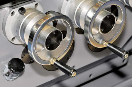 Two round metal handles of the lathe. Shallow depth of field