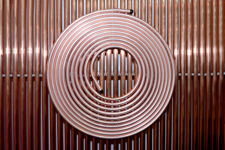 Copper tubes for cooling systems, air conditioners as an industrial background. Copper tubes rolled into a ring and straight