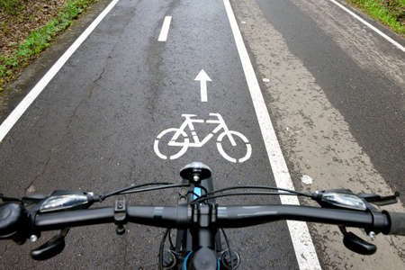 Bicycle on a bike path in a summer forest. Bicycle lane signage on a street. Focus on the middle ground Standard-Bild