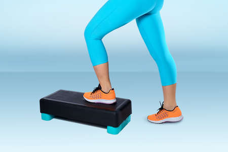 Woman in orange sneakers and turquoise sportswear do exercise on fitness step on blue