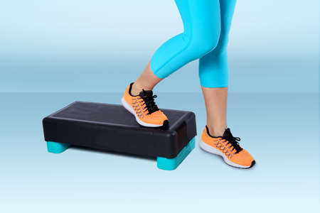 Woman in orange sneakers and turquoise sportswear do exercise on a black-turquoise aerobic and fitness step on blue