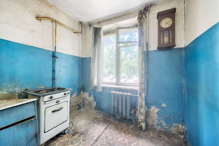 Old ugly abandoned empty kitchen in a residential building. The interior of the collapsing room of the kitchen in the house Standard-Bild