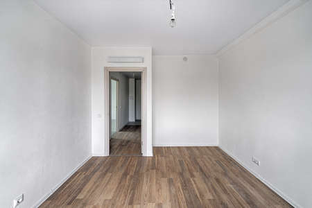 Empty room after repairs in an apartment building. Fresh renovated room with wooden floor Standard-Bild