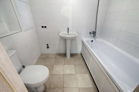 Small new bathroom with toilet, sink, bathtub. Placement of a bathroom in a new apartment