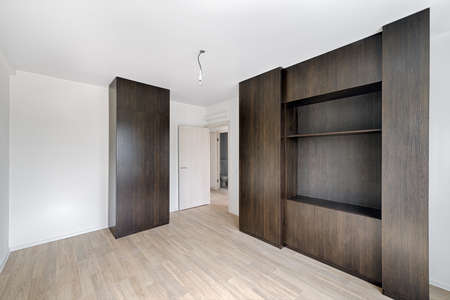 Half-empty room with wardrobes after repairs in an apartment building. Fresh renovated room with wooden floor