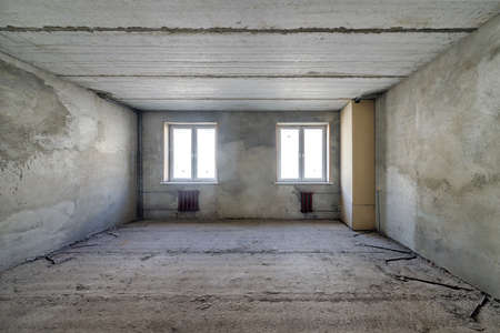 Empty living room in a country house without repair. Unfinished room with concrete walls and ceiling Standard-Bild