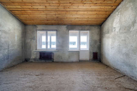 Empty living room in a country house without repair. Unfinished room with concrete walls and wooden beams on the ceiling