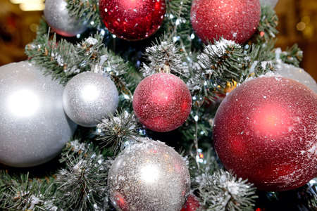 Red and silver Christmas balls on Christmas tree. Close up Standard-Bild
