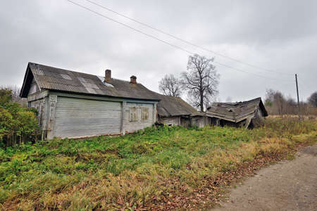 Ruined wooden farmhouse and barn. Abandoned village house. Concept: devastation, depression, decline of rural life