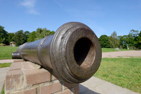 Barrel of an old-fashioned cast-iron cannon. Ancient historical artillery gun Standard-Bild