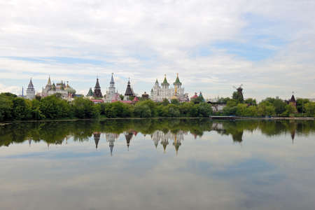Kremlin in the Moscow district of Izmailovo on a summer day. View of the Izmailovsky Kremlin - a complex of buildings in the old Russian style and their reflection in the water of the pond