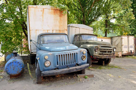 Moscow, Russia - August 23, 2020: Old rusty trucks made in the USSR, brands GAZ and ZIL. The most popular trucks of the USSR in an abandoned parking lot