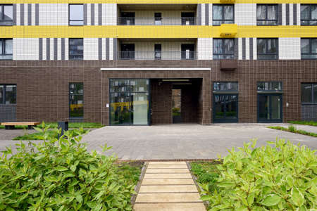 Typical modern entrance to the staircase of an apartment building. Path, lawn with plants in front of the entrance Standard-Bild