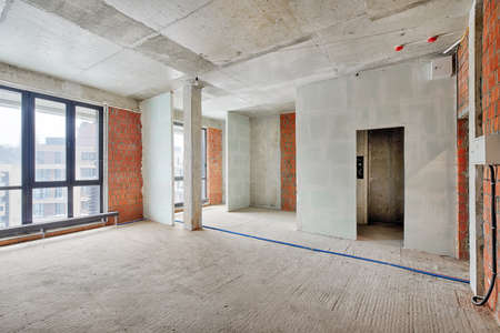 Empty living room without renovation, no repair in a new apartment building. Living room with concrete walls, floor and ceiling, no plaster