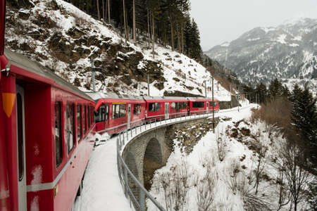 POSCHIAVO, SWITZERLAND - January, 2018. The train Bernina Express, crosses the Swiss alps in winter with snow