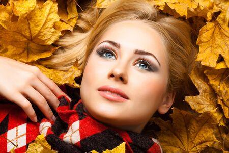 The beautiful blonde in autumn foliage