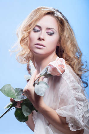 The beautiful blond girl with winter cosmetics and a rose Stock Photo