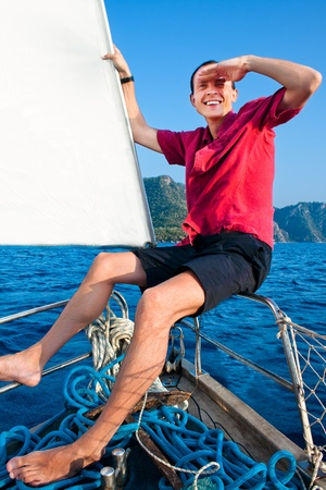 smiling young man on the yacht looks afar