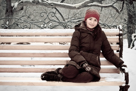 young woman in a red cap in winter park on a bench
