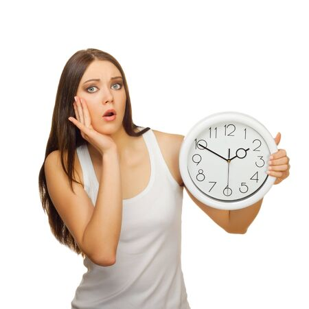 The young woman with clock is upset and surprised, on a white background