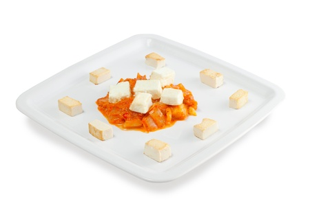 Slices of fried cheese with grilled vegetables on a white background