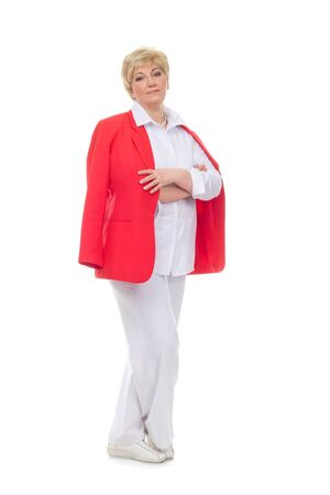 Portrait of a smiling adult woman in a red jacket standing with folded hands isolated against white background Stock Photo
