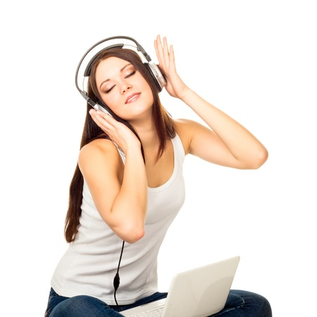 Beautiful girl listens to music through ear-phones on a white background