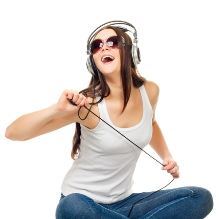 Beautiful girl listens to music through earphones on a white background