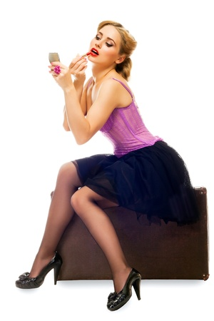 The blonde pretty woman waits, sits on a suitcase and puts on lipstick on white background photo