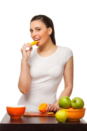 Beautiful young woman eating segments of an orange  on white background photo