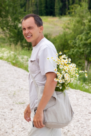 the young man with camomiles in a bag looks back Stock Photo