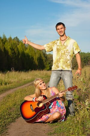 young man and woman with guitar  hippie hitch-hike photo
