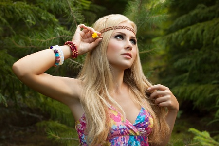 beautiful young woman in wood decorates hair with flower  style of hippie